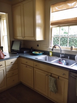 tired kitchen counters, sink, and shade fabric